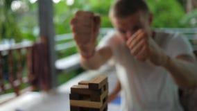 Giovane bastone pazzo di Put Wooden Block dell'uomo d'affari sulla cima della torre Metraggio lento del gioco della Tabella di HD archivi video