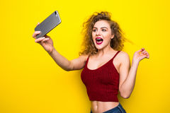 Giovane beautifulgirl con un'acconciatura riccia La ragazza di risata prende il selfie dal telefono su fondo giallo Immagini Stock Libere da Diritti