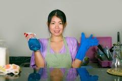 Giovane bei e pulizia e lavaggio cinesi asiatici felici della donna con la cucina della bottiglia dello spruzzo a casa in guanti  fotografia stock