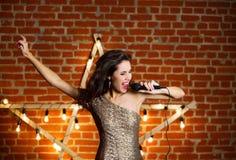 Giovane bella canzone di canto della donna sopra la stella di legno con luminoso Fotografia Stock