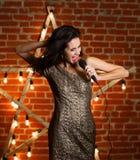 Giovane bella canzone di canto della donna sopra la stella di legno con luminoso Fotografie Stock Libere da Diritti