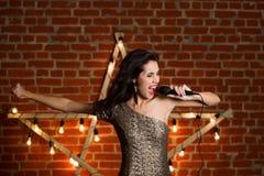 Giovane bella canzone di canto della donna sopra la stella di legno con luminoso Fotografie Stock