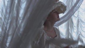 Giovane bella donna in abito di palla e condizione bianca del cappello sui precedenti delle tende trasparenti e della piuma d'ond video d archivio