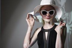 Giovane bella donna alla moda con trucco d'avanguardia Macchina fotografica di sguardo di modello, occhiali alla moda d'uso, capp Immagine Stock