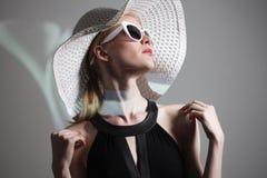 Giovane bella donna alla moda con trucco d'avanguardia Macchina fotografica di sguardo di modello, occhiali alla moda d'uso, capp Immagini Stock