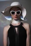 Giovane bella donna alla moda con trucco d'avanguardia Macchina fotografica di sguardo di modello, occhiali alla moda d'uso, capp Fotografie Stock Libere da Diritti