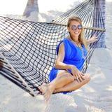 Giovane bella donna alla moda nel layin blu degli occhiali da sole e del vestito fotografia stock libera da diritti