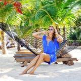 Giovane bella donna alla moda nel layin blu degli occhiali da sole e del vestito immagine stock libera da diritti