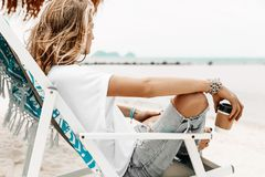 Giovane bella donna alla moda nell'abbigliamento casual che si rilassa nella sedia o Fotografie Stock