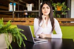 Giovane bella donna allegra che esamina macchina fotografica con il sorriso mentre sedendosi al suo posto di lavoro Immagini Stock