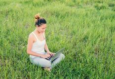 Giovane bella donna asiatica che per mezzo del computer portatile sui prati della natura Immagine Stock