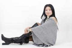 Giovane bella donna asiatica che si siede su un fondo leggero Immagini Stock