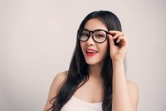 Giovane bella donna asiatica con i vetri d'uso del fronte sorridente Immagini Stock