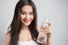 Giovane bella donna asiatica con il holdin sorridente delle labbra di rosso e del fronte Immagini Stock Libere da Diritti