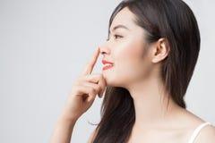 Giovane bella donna asiatica con il tocco sorridente delle labbra di rosso e del fronte Fotografia Stock Libera da Diritti