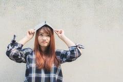 Giovane bella donna asiatica sorridente che pensa con un libro al di sopra sul fondo del muro di cemento Fotografia Stock