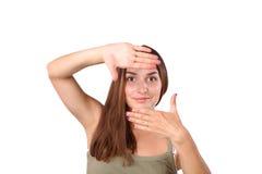 Giovane bella donna attraente che incornicia le sue mani Fotografie Stock Libere da Diritti