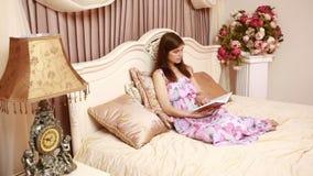 Giovane bella donna attraente, ragazza, leggendo un libro, risiedente in un letto di lusso in una camera di albergo camera da let video d archivio