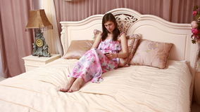 Giovane bella donna attraente, ragazza, leggendo un libro, risiedente in un letto di lusso in una camera di albergo camera da let stock footage