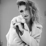 Giovane bella donna bionda che posa in cappotto all'aperto Fotografie Stock Libere da Diritti