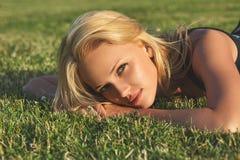 Giovane bella donna bionda che si rilassa su un prato immagini stock