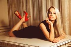 Giovane bella donna bionda che si trova sulla tavola con lo sguardo di seduzione Fotografia Stock Libera da Diritti