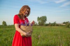 Giovane bella donna bionda che smilling con i fiori in natura di estate fotografia stock