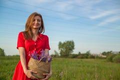 Giovane bella donna bionda che smilling con i fiori in natura di estate immagine stock