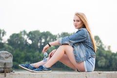 Giovane bella donna bionda in pantaloncini corti e jeans che si siedono sul lungomare di estate e che esaminano la macchina fotog immagine stock