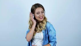 Giovane bella donna bionda sexy che ascolta la musica in cuffie su fondo bianco isolato archivi video