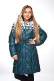 Giovane bella donna bionda in un cappotto lungo con il cappuccio della pelliccia fotografia stock libera da diritti