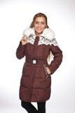 Giovane bella donna bionda in un cappotto lungo con il cappuccio della pelliccia immagine stock