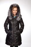 Giovane bella donna bionda in un cappotto lungo con il cappuccio della pelliccia fotografia stock