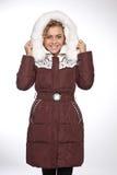 Giovane bella donna bionda in un cappotto lungo con il cappuccio della pelliccia royalty illustrazione gratis