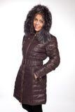 Giovane bella donna bionda in un cappotto lungo con il cappuccio della pelliccia immagine stock libera da diritti