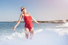 Giovane bella donna caicasian in costume da bagno rosso divertendosi spruzzatura sull'onda alla gravidanza felice della costa del fotografie stock
