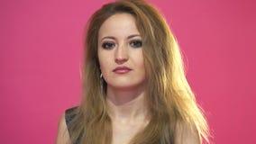 Giovane bella donna calma con capelli marroni che dice no e che scuote testa nell'incredulità su fondo rosa archivi video
