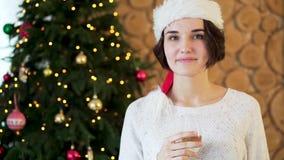 Giovane, bella donna in cappello di Santa Claus e vetro di champagne sopra il salone e fondo dell'albero di Natale, partito stock footage