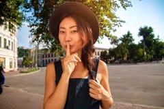 Giovane bella donna castana che mostra il segno di silenzio con il dito sulle labbra all'aperto fotografia stock