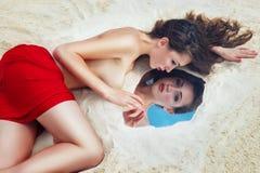 Giovane bella donna castana con tessuto rosso sul lyi delle coscie immagine stock