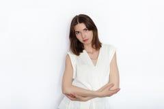 Giovane bella donna castana del modello del principiante nella posa di pratica della blusa bianca mostrando le emozioni sul fondo immagini stock