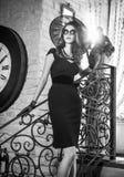 Giovane bella donna castana nella condizione nera sulle scale vicino ad un orologio di parete graduato eccessivo Signora misterio Fotografia Stock