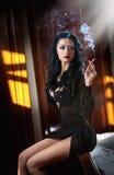 Giovane bella donna castana in vestito nero che si rilassa sul nel paesaggio d'annata Giovane signora misteriosa romantica Fotografie Stock