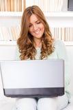 Giovane bella donna casuale che per mezzo di un computer portatile a casa Fotografie Stock