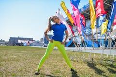 Giovane bella donna caucasica che fa allenamento di forma fisica e che posa sull'erba verde allo stadio Fotografia Stock Libera da Diritti