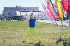 Giovane bella donna caucasica che fa allenamento di forma fisica su erba verde allo stadio Fotografia Stock