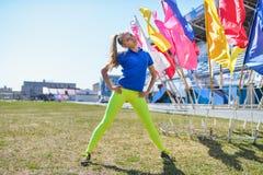 Giovane bella donna caucasica che fa allenamento di forma fisica su erba verde allo stadio Immagini Stock Libere da Diritti