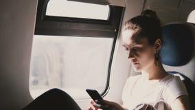 Giovane bella donna caucasica che per mezzo dello smartphone che si siede sul sedile di finestra del treno, messaggi di battitura archivi video