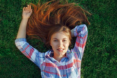 Giovane bella donna caucasica con capelli rossi che si trovano sull'erba in camicia di plaid Fotografie Stock Libere da Diritti