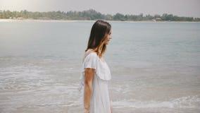 Giovane bella donna caucasica felice che cammina lungo la spiaggia tropicale idilliaca dell'oceano con le onde calme che si rilas video d archivio